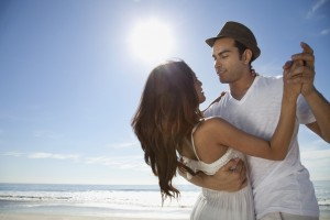 Young couple dancing on sandy beach